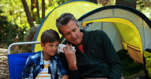 Father and son using mobile phone outside tent. At campsite stock video