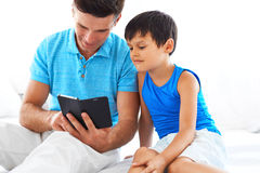 Father and son using mobile phone. Father showing son how to use mobile phone. Happy family spending leisure time together Stock Images
