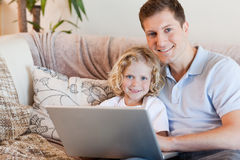 Father and son using notebook. On the sofa Stock Image