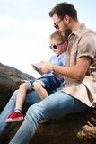 Father and son using smartphone on stones. At park royalty free stock image