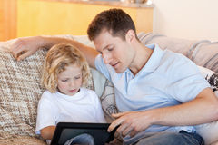 Father and son using tablet on the sofa Royalty Free Stock Images