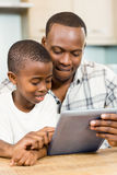 Father and son using tablet together Stock Photography