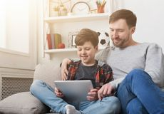 Father and son using tablet together on sofa at home stock image