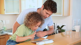 Father and son using a touchpad. In the kitchen stock footage