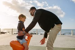 Father and son on vacation. Boy enjoys sitting on a rotating chair near seafront. Man with his son on a vacation enjoying near the sea Royalty Free Stock Image