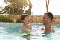 Father And Son On Vacation Having Fun In Outdoor Pool Stock Photos