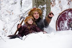 Portrait strong viking warrior winter woods battle scandinavian traditional clothing lumberjack chain mail leather spear deep fore. Father and son Vikings in a Royalty Free Stock Photos