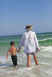 Father and Son Wading out into the Ocean Stock Photo