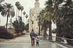 Father and son on the walk around Tore del Oro - Seville Spain. Father and son are walking on the promenade near Tore del Oro in the Seville city in Spain royalty free stock photography