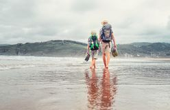 Father with son walk barefoot on the sand ocean beach royalty free stock photography