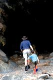 Father and son walk into cave Stock Photos