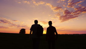 Father and son are walking along the field at sunset. View from the back, the father carries a backpack. Concept - new. Silhouettes of two men - son and father stock footage