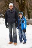 Father And Son Walking Along Snowy Street Royalty Free Stock Image