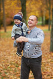Father with son walking in autumn forest Stock Image