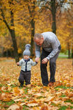 Father with son walking in autumn forest Stock Photo
