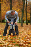 Father with son walking in autumn forest Royalty Free Stock Image