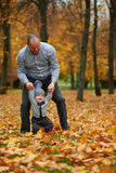 Father with son walking in autumn forest Stock Photography