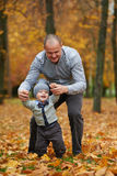 Father with son walking in autumn forest Royalty Free Stock Photo