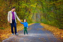 Father and son walking the autumn forest road Royalty Free Stock Image