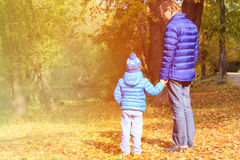 Father and son walking in autumn park Stock Photos