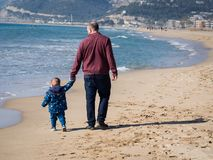 Father and son walking on the beach stock images