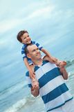 Father and son walking on beach Royalty Free Stock Photos