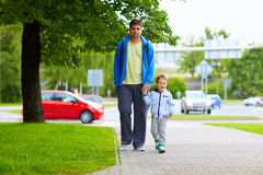 Father and son walking on city street Royalty Free Stock Photo
