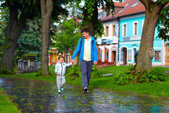 Father and son walking the city street after rain Royalty Free Stock Photography