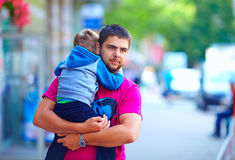 Father with son walking the colorful street Stock Photos