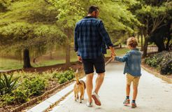 Father and son walking with a dog in the park. Rear view of father and son with dog walking in a park. Man holding hand on his little boy walking and talking royalty free stock photography
