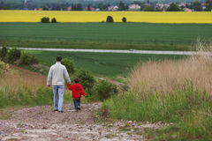 Father and son, walking in a field Royalty Free Stock Image