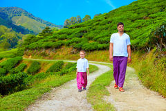 Father and son walking footpath through tea plantation Stock Photo