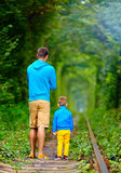 Father and son walking in green tunnel Stock Photo