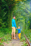 Father and son walking in green tunnel Stock Photos