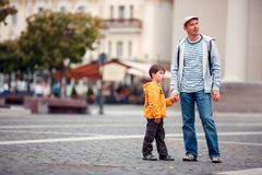 Father and son walking outdoors in city Stock Image