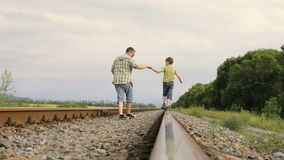 Father and son walking  on the railway at the day time. People having fun outdoors. Concept of friendly family