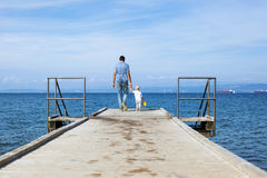 Father with son walking on the sea pier. Stock Photo