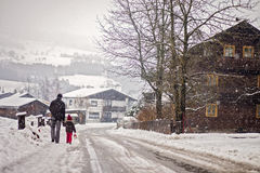 Father and son, walking in the snowy day in a village Stock Photography