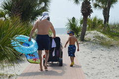 Father and son walking to beach. Father and young son in swimwear walking on a path toward the ocean, carrying swim toys and accessories Royalty Free Stock Photos