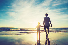 Father and Son Walking Together Holding Hands. Father and Son Holding Hands Walking Together on the Beach at Sunset Stock Photography