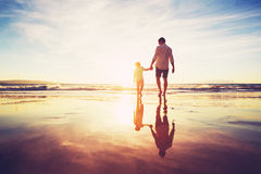 Father and Son Walking Together Holding Hands. Father and Son Holding Hands Walking Together on the Beach at Sunset Royalty Free Stock Photo