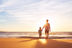 Father and Son Walking Together Holding Hands. Father and Son Holding Hands Walking Together on the Beach at Sunset Royalty Free Stock Images