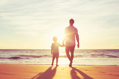 Father and Son Walking Together Holding Hands. Father and Son Holding Hands Walking Together on the Beach at Sunset Stock Image