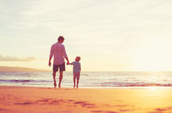 Father and Son Walking Together Holding Hands. Father and Son Holding Hands Walking Together on the Beach at Sunset Royalty Free Stock Photos