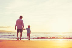 Father and Son Walking Together Holding Hands. Father and Son Holding Hands Walking Together on the Beach at Sunset Stock Photo