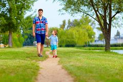 Father and son walking together in park Stock Photo