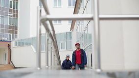 Father and son walking on the wheelchair ramp. Father and son holding hands and walking on the wheelchair ramp. They wear warm jackets. It is a cloudy spring stock video