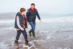 Father And Son Walking On Winter Beach Stock Photography