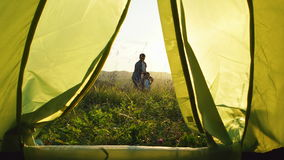 Father with son walks (go and back). View from the tent at the sunset stock video footage