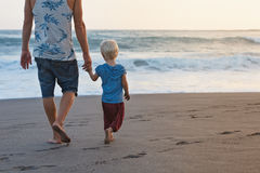 Father and son walks on sunset ocean beach. Happy family - barefoot father holds baby son hands, walk with fun along sunset sea surf on black sand beach. Travel stock image